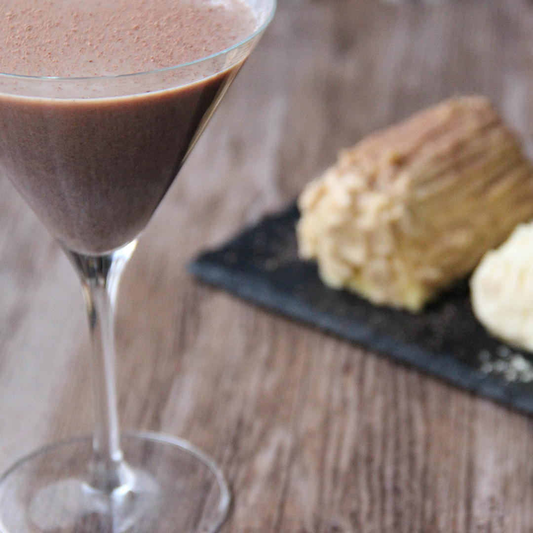 Picture of a martini glass of dark brown whiskey cocoa cocktail adorned with grated chocolate (in the left front corner). Behind the glass are two mini individual size Christmas logs, one white vanilla flavored and one brown coffee flavor on top of a black rectangular slate plate (in the right bottom corner). The glass and the plate are set on a brown wooden table.