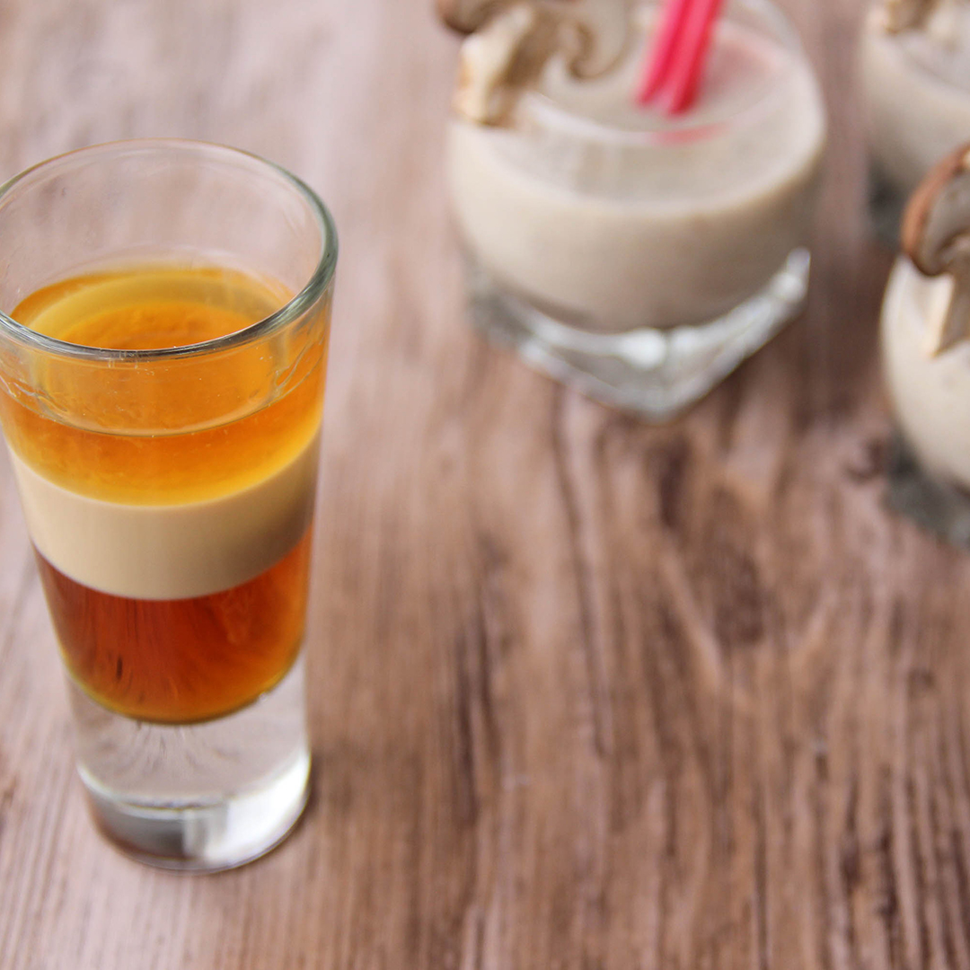 Picture of a clear glass shot glass filled with the three color layered cocktail A.B.C cocktail (in the left front corner). Behind the shot glass are three clear glass individual size serving bowls of mushroom velouté adorned with a slice of brown button mushroom and pink straws (in the right bottom corner). The cocktail and the bowls are set on a brown wooden table.