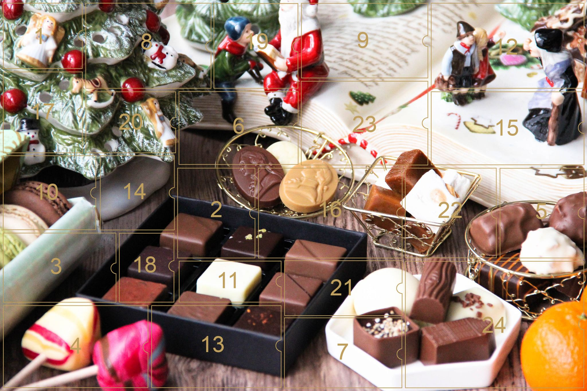 Picture of a mix of porcelain figurines representing a Christmas scenery, next to a Christmas porcelain tree and chocolates and nice treats gathered in different kinds of white porcelain small tray, small chocolate boxes and gold wire trays. All divided in 24 advent calendar sections.