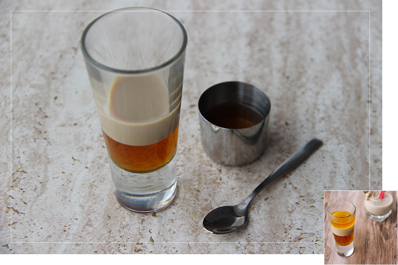 Picture of a shot glass layer filled with Amaretto and Baileys Irish cream next to a shot of Cognac and a spoon.