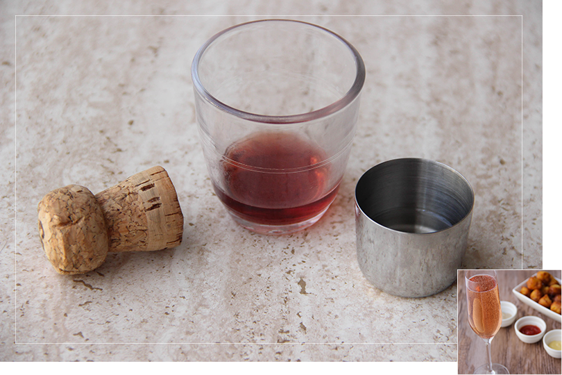 Picture of a glass of a glass of raspberry creme next to a measuring jigger filled with sugar syrup next to a cork from a champagne bottle