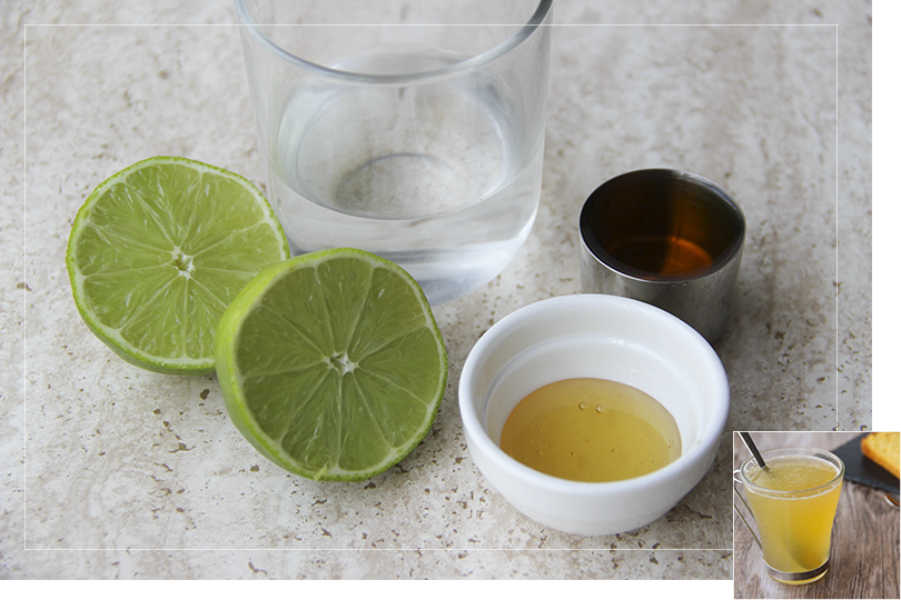 Picture of the different non-branded ingredients required for the hot grog cocktail with from left to right:  a lime sliced in half, a glass of water, a cup of liquid honey and a shot of rum on a quartz table.