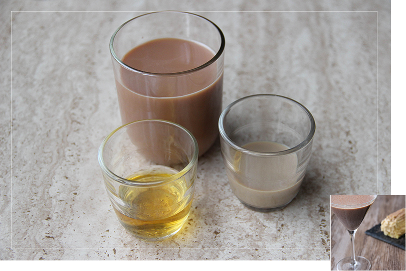 Picture of a glass of cold cocoa next to a shot of Baileys Irish cream and a shot of whiskey on a quartz table.