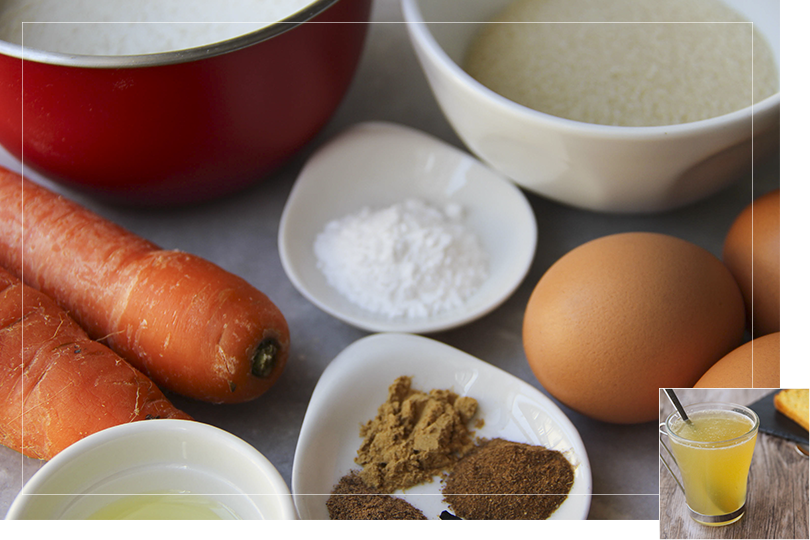 Picture of the different non-branded ingredients required for a carrot cake with from left to right: a mixing bowl filled with plain flour, two carrots, a white porcelain cup of oil, a white porcelain cup with the cinnamon powder, the nutmeg powder and the ginger powder, a white porcelain cup of baking powder, a white porcelain bowl of brown sugar and three eggs on a grey marble table.