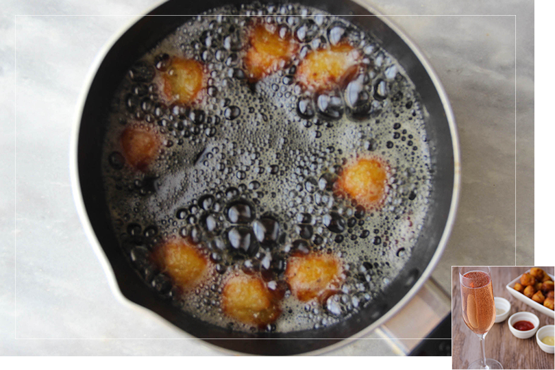 Picture of a saucepan filled with frying oil and Pommes Dauphines being fried on a marble table.