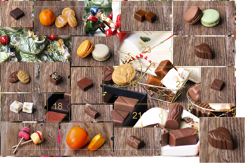 Picture of a mix of porcelain figurines representing a Christmas scenery, next to a Christmas porcelain tree and chocolates and nice treats. All divided in 24 advent calendar sections that are being uncovered each day. Section 15 is a picture of a leaf shape milk chocolate bite size on a dark wood table.