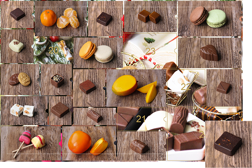 Picture of a mix of porcelain figurines representing a Christmas scenery, next to a Christmas porcelain tree and chocolates and nice treats. All divided in 24 advent calendar sections that are being uncovered each day. Section 19 is a picture of a square shape dark chocolate bite with espelette red pepper sprinkled on top, on a dark wood table.