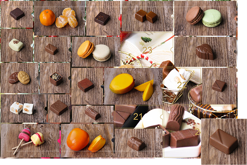 Picture of a mix of porcelain figurines representing a Christmas scenery, next to a Christmas porcelain tree and chocolates and nice treats. All divided in 24 advent calendar sections that are being uncovered each day. Section 20 is a picture of a rectangular shape brown chocolate bite with irregularities on top, on a dark wood table.