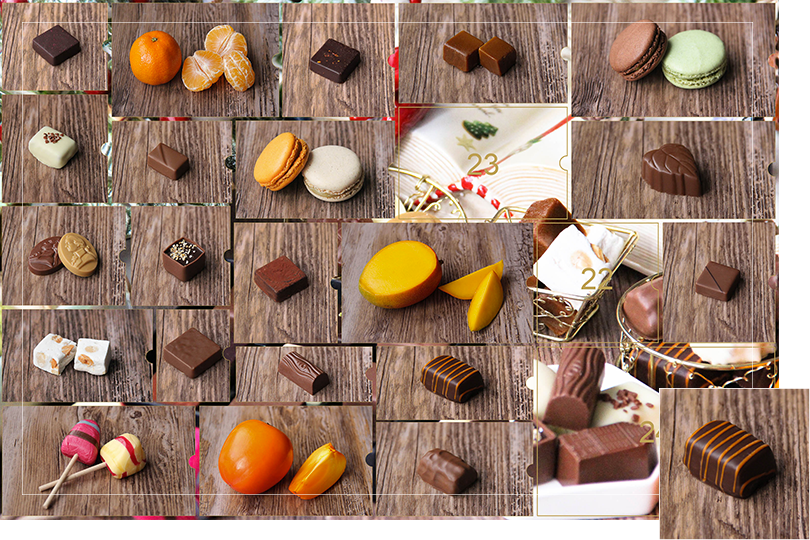 Picture of a mix of porcelain figurines representing a Christmas scenery, next to a Christmas porcelain tree and chocolates and nice treats. All divided in 24 advent calendar sections that are being uncovered each day. Section 21 is a picture of a rectangular shape dark chocolate bite with orange candied strips on top, on a dark wood table.