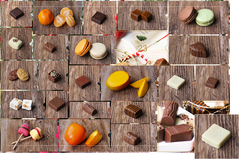 Picture of a mix of porcelain figurines representing a Christmas scenery, next to a Christmas porcelain tree and chocolates and nice treats. All divided in 24 advent calendar sections that are being uncovered each day. Section 22 is a picture of a square shape white chocolate bite on a dark wood table.