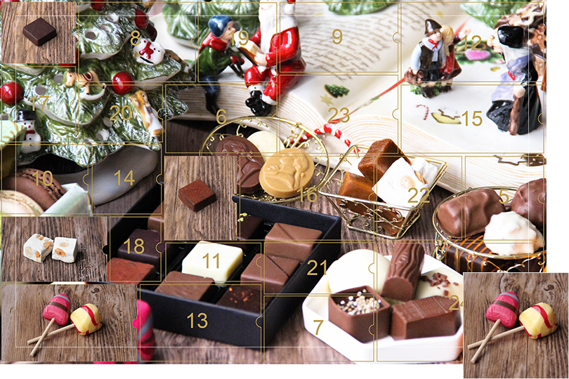 Picture of a mix of porcelain figurines representing a Christmas scenery, next to a Christmas porcelain tree and chocolates and nice treats. All divided in 24 advent calendar sections, with the fourth section, being a picture of two colourful round triangular shape lolly. One red with brown and blue stripes and one yellow with yellow and red stripes on a dark wood table, as if the calendar has been opened.