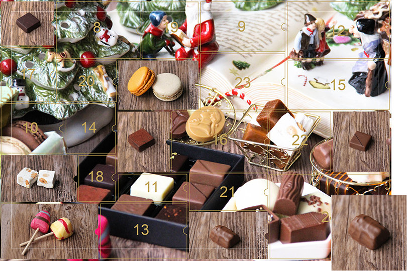 Picture of a mix of porcelain figurines representing a Christmas scenery, next to a Christmas porcelain tree and chocolates and nice treats. All divided in 24 advent calendar sections that are being uncovered each day. Section 7 is a picture of a milk chocolate log bite, on a dark wood table.
