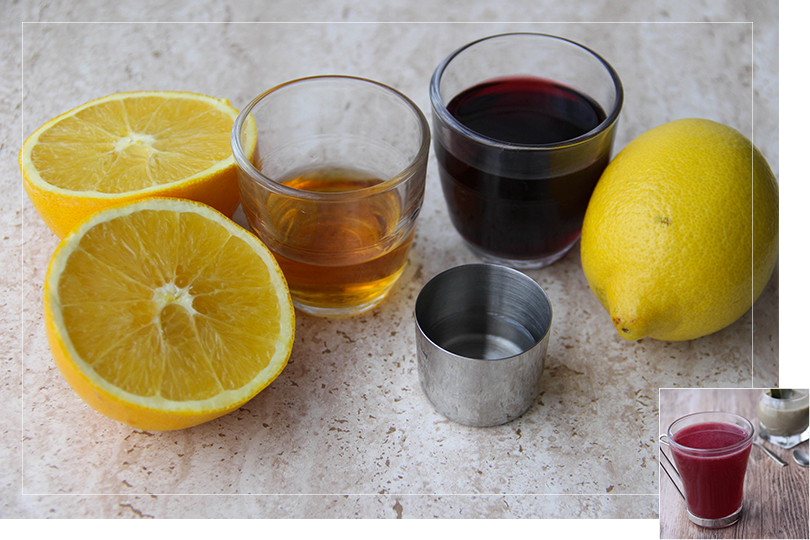 Picture of the ingredients required for the Hot Red French cocktail namely from left to right: an orange sliced in half, a shot glass of Grand marnier, a shot glass of sugar cane syrup, a shot glass of claret red wine and a lemon on a quartz table.