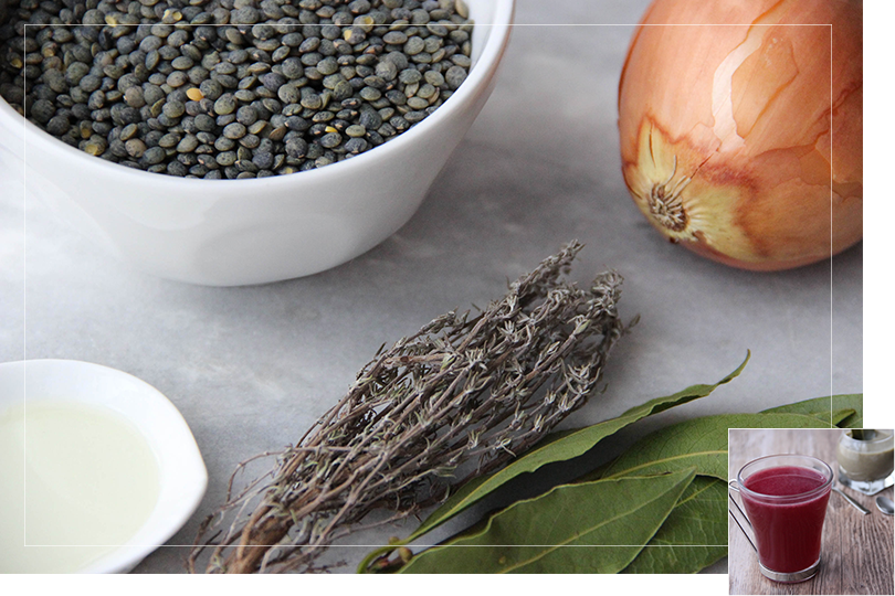Picture of the different non-branded ingredients required for a lentil velouté with from left to right: a cup of oil, a white porcelain bowl of lentil, a bunch of bunched thyme, a bunch of fresh bay leaves and a sweet onion on a marble table.
