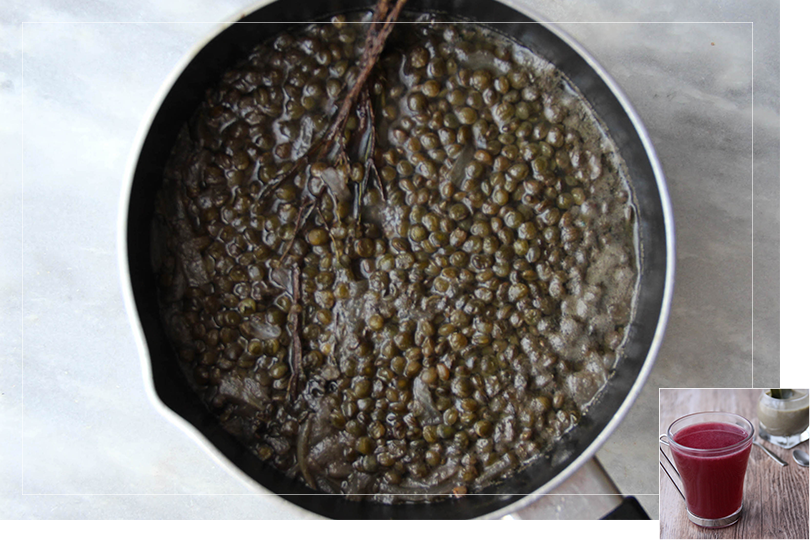 Picture of a saucepan filled with lentils, sweet onion bunched thyme and bay leaves on a marble table.