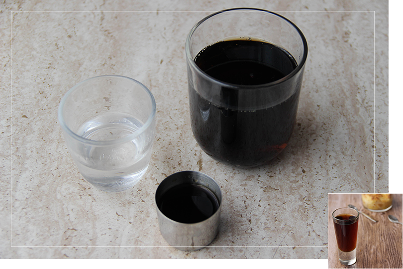 Picture of the ingredients required for an Assisted Suicide cocktail namely from left to right a shot glass of white rum, a shot of jägermeister and a glass of coke in a quartz table.