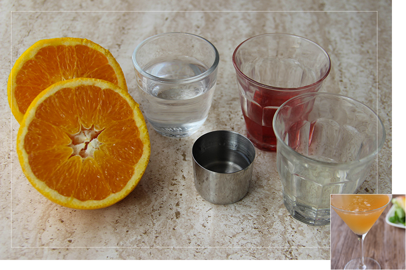 Picture of the ingredients required for a tango martini cocktail namely from left to right: an orange sliced in half, a shot glass of gin, a shot of orange curaçao liqueur, a shot of martini and a shot of vermouth on a quartz table.