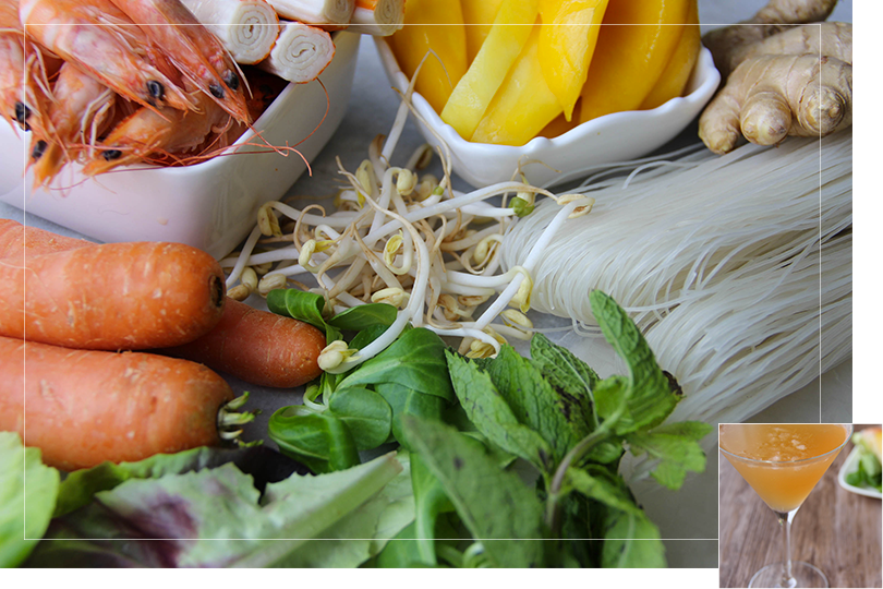 Picture of the different non-branded ingredients required for spring rolls with from left to right: carrots, a square white porcelain cup half filled with shrimps and half filled with surimi pieces, salad, mint leaves, mungo beens, a square white porcelain bowl filled with mango slices, a chunk of ginger and rice vermicelli noodles and rice papers on a marble table.