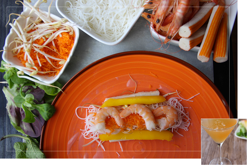 Picture of a big circle orange plate with a watered rice transparent rice paper filled with cooked rice vermicelli noodles, grated carrots, three cooked shrimps, two slices of surimi and two slices of mango, next to salad leaves, a square white bowl of grated carrots and mungo beans, next to a square white porcelain bowl of cooked rice vermicelli noodles next to a square white porcelain bowl half filled with cooked shrimps, half filled with surimi sticks on a marble surface on a black wood table.
