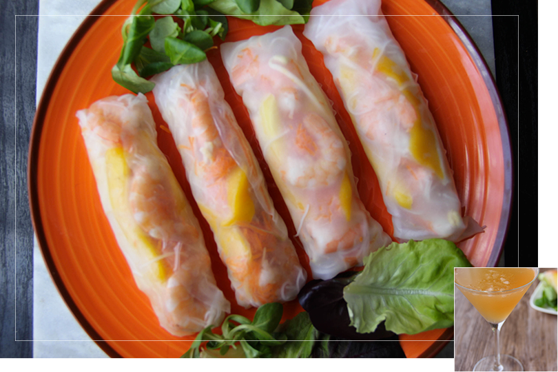 Picture of a big orange plate with brown corners, filled with four fully mounted spring rolls next to salad leaves on a marble surface on a black wood table.
