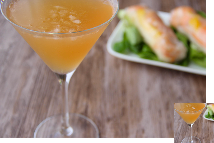 Repeat of the first picture of the article in a slightly different picture format: Picture of a martini glass of tango martini cocktail (in the left front corner) in front of two spring rolls on salad leaves on a white porcelain rectangular plate (in the right bottom corner) in a brown wooden table.