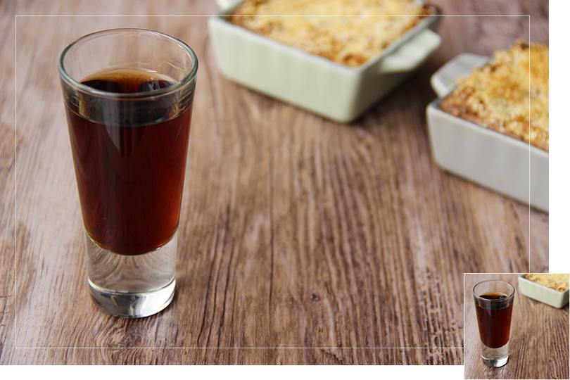 Repeat of the first picture of the article in a slightly different picture format: Picture of a shot glass of Buona sera cocktail (in the left front corner) in front of two individual size porcelain baking tin filled with minced meat parmentier (in the right bottom corner) on a brown wooden table.