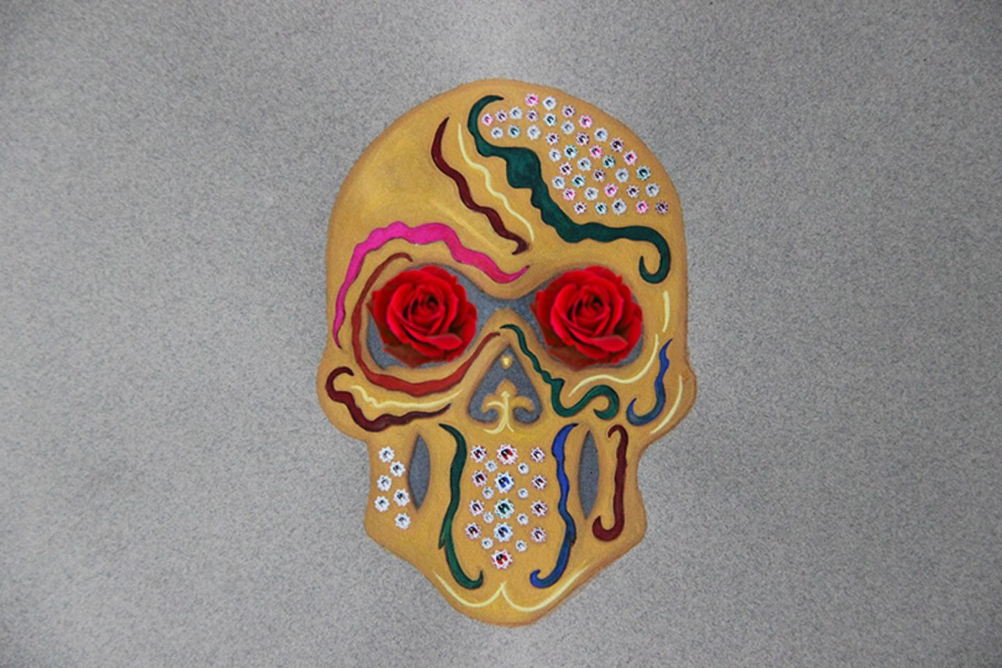 Painting of a face skeleton looking up front with red roses in the orbit as eyes adorned with multi coloured precious stones and multi coloured enamels.