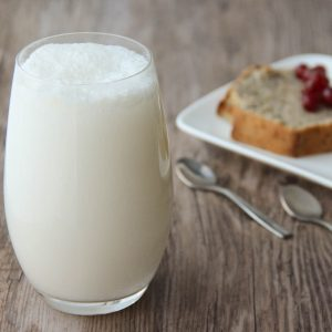 Picture of a collins glass of white Fizz violette cocktail (in the left front corner). Behind the glass are two slices of banana nut bread on top of a white porcelain rectangular plate adorned with redcurrant (in the right bottom corner). The glass and the plate are set on a brown wooden table.