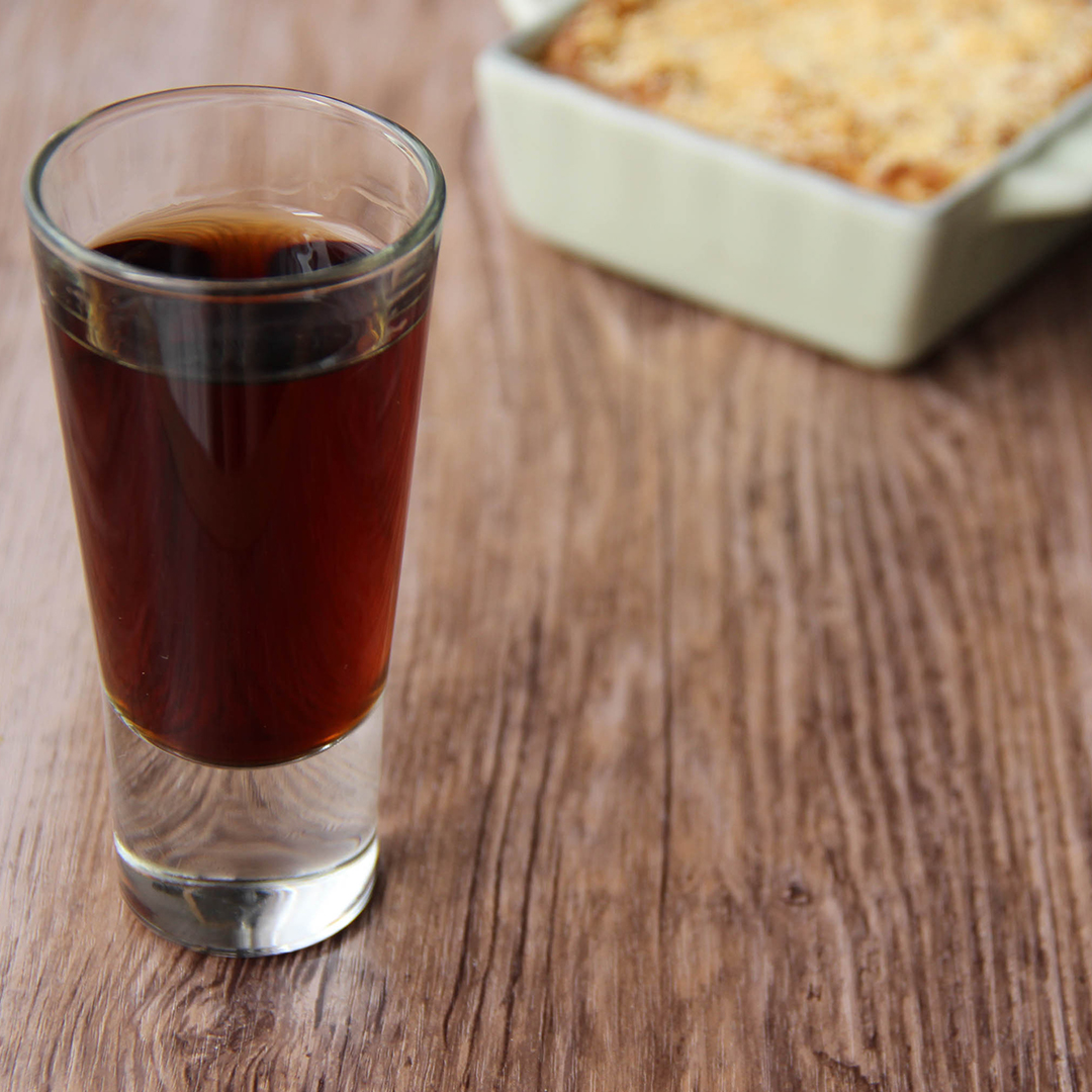 Picture of a clear glass shot glass of brown Buena sera cocktail (in the left front corner). Behind the glass are two individual size square green and grey porcelain baking tray filled with minced meat parmentier (in the right bottom corner). The glass and the minced meat parmentier are set on a brown wooden table.