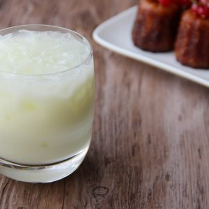 Picture of an old fashioned glass of opac paste green Swiss absinthe cocktail (in the left front corner). Behind the glass is a rectangular white porcelain plate filled with six medium size cannelés adorned with redcurrant on top (in the right bottom corner). The glass and the plate are set on a brown wooden table.