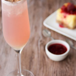Picture of a flute glass of bright pastel pink Hollywood cocktail (in the left front corner). Behind the glass are two individual size cheesecakes, one square shaped and one circle shaped, on a white rectangular porcelain plate next to a cup of strawberry sauce (in the right bottom corner). The glass and the plate are set on a brown wooden table.