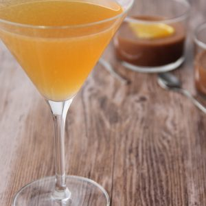 Picture of a martini glass of transparent bright orange Dorian grey cocktail (in the left front corner). Behind the glass are two clear glass individual size cups of chocolate mousse adorned with an orange quarter slice (in the right bottom corner). The glass and the cups are set on a brown wooden table.