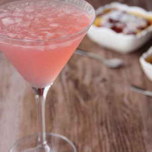Picture of a martini glass of pink Sloppy Joe cocktail (in the left front corner). Behind the glass are two individual size white porcelain square bowls of cherry clafoutis (in the right bottom corner). The glass and the bowls are set in a brown wooden table.