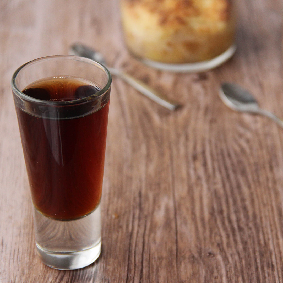 Picture of a clear glass shot glass of dark brown Assisted suicide cocktail (in the left front corner). Behind the glass are two clear glass individual size cups of apple and pear crumbles (in the right bottom corner). The glass and the individual size cups are set on a brown wooden table.