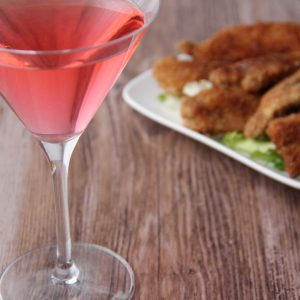 Picture of a martini glass of transparent pink Martini litchi cocktail (in the left front corner). Behind the glass is a rectangular white porcelain plate filled with chicken nuggets and adorned with salad leaves (in the right bottom corner).The glass and the plate are set on a brown wooden table.
