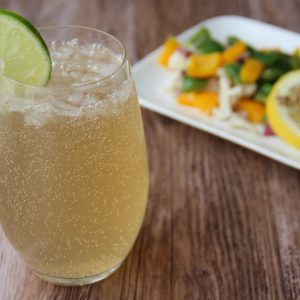 Picture of a collins glass of transparent yellow ginger beer daiquiri cocktail adorned with a slice of lime (in the left front corner). Behind the glass is a rectangular white porcelain plate filled with fish papillate and vegetables, adorned with a slice of lemon and spices (in the right bottom corner). The glass and the plate are set on a brown wooden table.