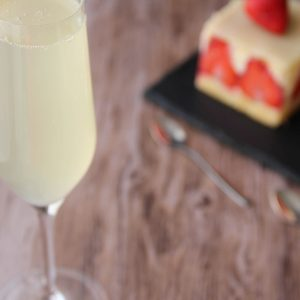 Picture of a flute glass of light yellow green French 75 cocktail (in the left front corner). Behind the glass are two individual size strawberry cakes, one square shape and the other one round shape both on top of a black rectangular slate plate (in the right bottom corner). The glass and the plate are set on a brown wooden table.