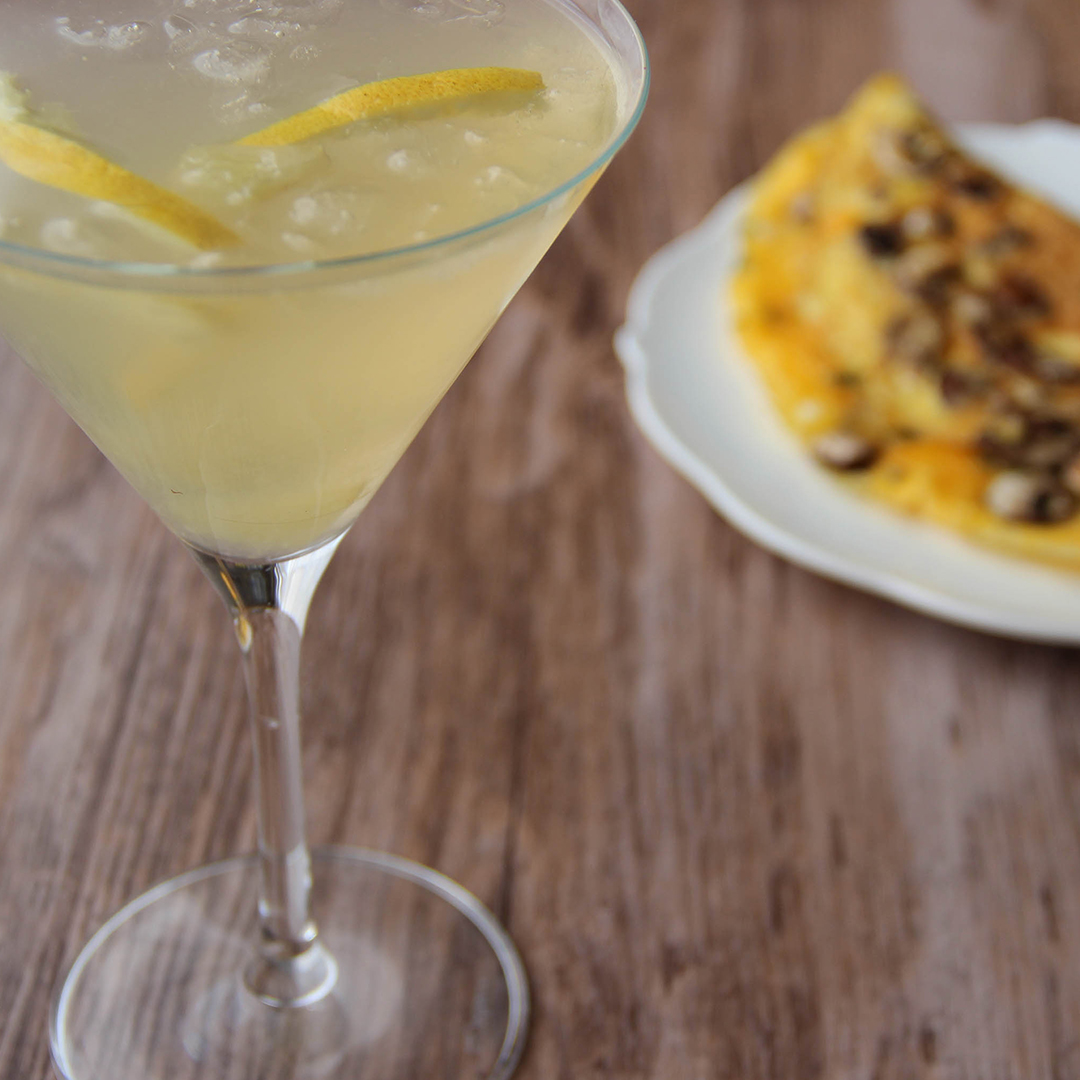 Picture of a martini glass of transparent yellow Honey bee cocktail garnished with lemon slices (in the left front corner). Behind the glass is a white porcelain round plate with a half moon folded mushroom omelette on top (in the right bottom corner). The glass and the plate are set on a wooden table.