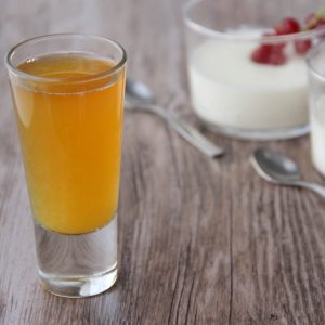 Picture of a clear glass shot glass of transparent orange California plates cocktail (in the left front corner). Behind the glass are small individual size clear glass verrines of panna cotta adorned with redcurrand (in the right bottom corner). The glass and the verrines are set on a brown wooden table.