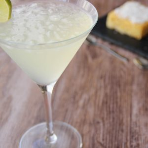 Picture of a martini glass of frozen margarita cocktail adorned with a slice of lime (in the left front corner). Behind the glass are two individual size pineapple coconut cakes, one square and one round shaped both on top of a black slate plate (in the right bottom corner). The glass and the plate are set on a brown wooden table.