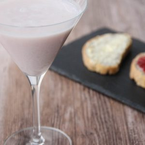 Picture of a pastel pink martini glass of ace cocktail (in the left front corner). Behind the glass are two slices of poppy seed bread, one with butter, the other one with strawberry jam on a rectangular black slate plate (in the right bottom corner). The glass and the plate are set on a brown wooden table.