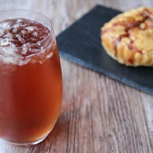 Picture of a Collins glass of dark orange Country breeze cocktail (in the left front corner). Behind the glass is an individual size mini quiche on top of a black rectangular slate plate (in the right bottom corner). The glass and the plate are set on a brown wooden table.