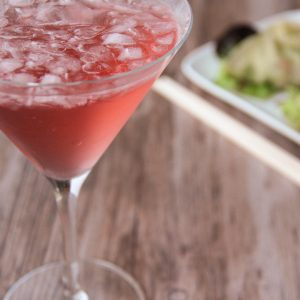 Picture of a martini glass of pink So-so martini cocktail (in the left front corner). Behind the glass is a rectangular white porcelain plate with two Chinese dumplings and Chinese sticks (in the right bottom corner). The glass and plate are set on a brown wooden table.