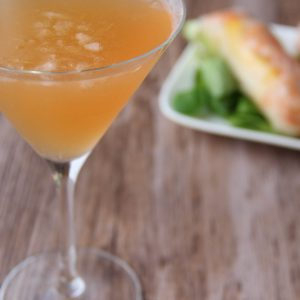 Picture of a martini glass of orange tango martini cocktail (in the left front corner). Behind the glass are two spring rolls on salad leaves on top of a white porcelain rectangular plate (in the right bottom corner). The glass and the plate are set in a wooden brown table.