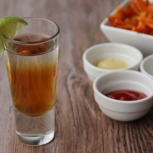Picture of a clear glass shot glass of Alice in wonderland cocktail, a two color layered shot adorned with a wedge of lime (in the left front corner): the bottom layer is orange and the top layer is transparent. Behind the glass is a rectangular white porcelain serving tray filled with sweet potato fries and next to three little terrines filled with side sauce ketchup, mayonnaise and mustard (in the right bottom corner). The glass, the tray and the little sauce cups are set on a brown wooden table.