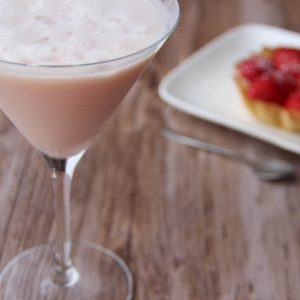 Picture of a martini glass of pastel pink blush martini cocktail (in the left front corner). Behind the glass is a white rectangular porcelain plate with an individual size strawberry pie on top (in the right bottom corner). The glass and the plate are set on a brown wooden table.