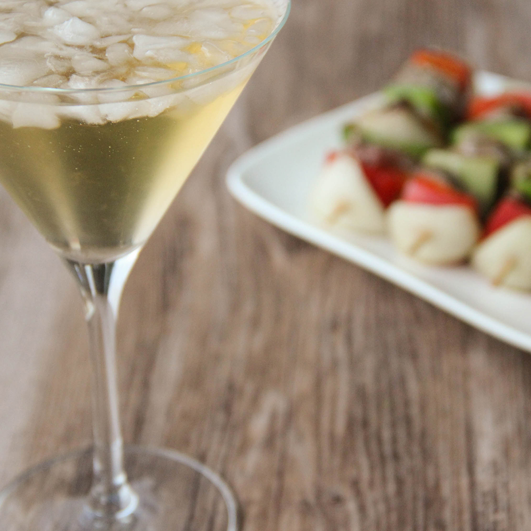 Picture of a martini glass of transparent yellow green apple martini cocktail (in the left front corner). Behind the glass is a white rectangular porcelain plate filled with little brochettes kebabs (in the right bottom corner). The glass and the plate are set on a brown wooden table.