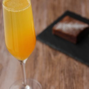 Picture of a flute glass of bubbly and yellow orange mimosa cocktail (in the left front corner). Behind the glass is rectangular black slate plate with a square shape individual size piece of chocolate fondant next to a cup of vanilla ice cream (in the right bottom corner). The glass and the plate are set on a brown wooden table.
