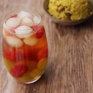 Picture of a collins glass of fruit cup cocktail adorned with lychee, grapes and raspberries (in the left front corner). Behind the glass are two bowls small individual size bowls of nasi goreng (in the right bottom corner). The glass and bowls on a brown wooden table.