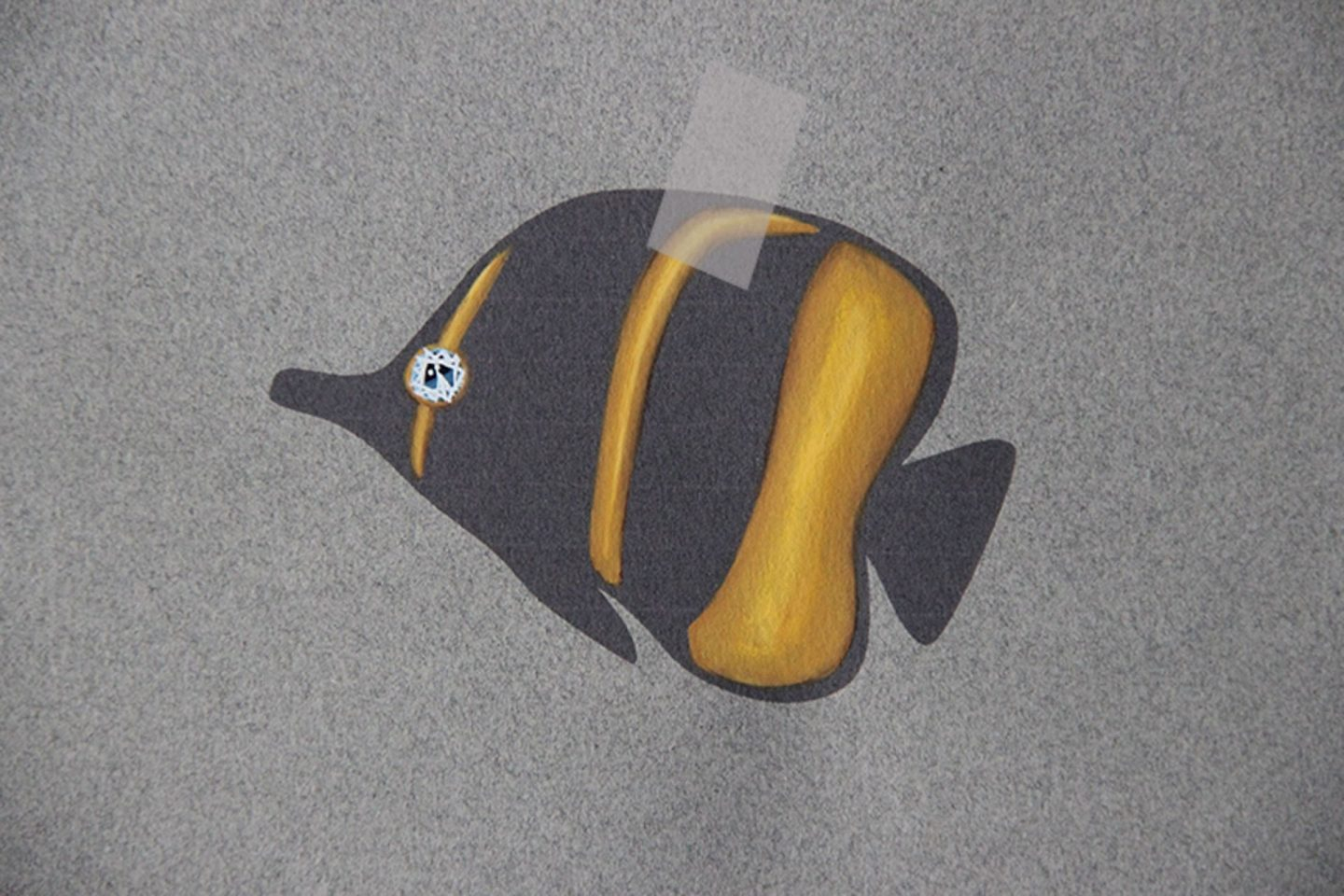 Painting of the drawing of an exotic fish paining black and gold with a sapphire precious stone set as its eye with sellotape on as if the fish is ready to be taped on someone's back as an April fool's prank.